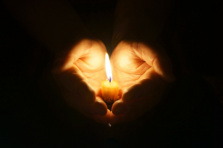 A candle held in a hand | NICRC