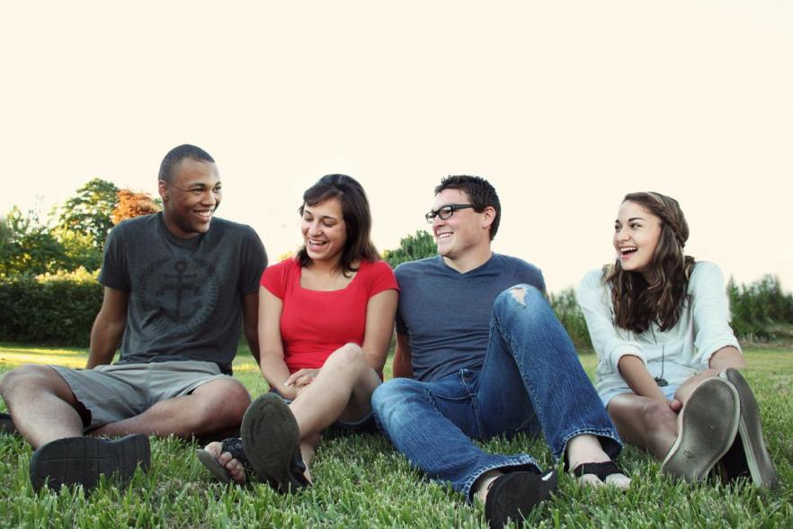 Four smiling people sitting on together on the grass | NI CRC