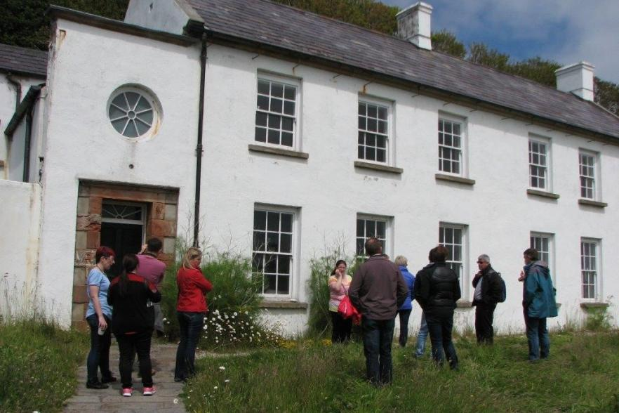 People gathered outside an old house   NICRC