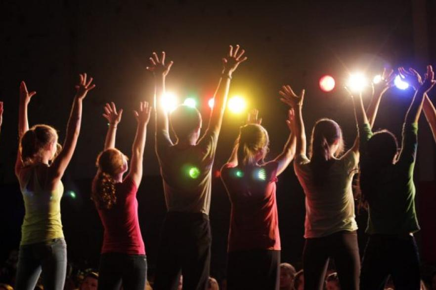 A crowd of people with their hands raised | CRC NI